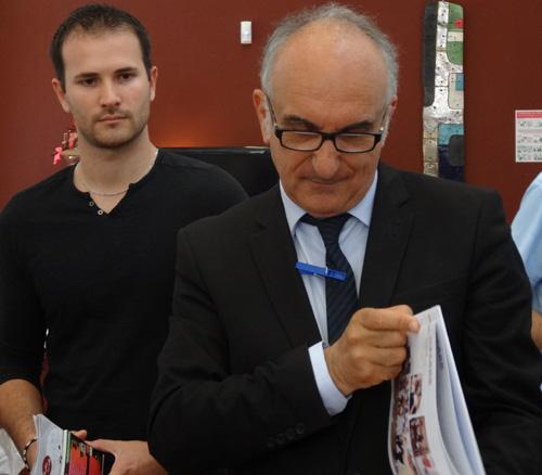 """Carlo Scibetta feuilletant son exemplaire du livre """"Oscarr 20 ans"""""""